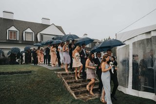 wedding-guests-walking-down-stairs-with-umbrellas-into-tented-wedding-venue-family-home