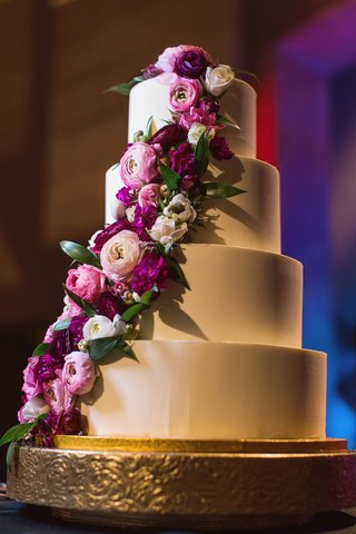 four-tier-wedding-cake-with-smooth-frosting-and-fresh-pink-flowers-cascading-down-the-side