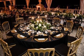 wedding-reception-table-gold-chairs-black-linens-and-napkins-gold-charger-plates-green-and-white