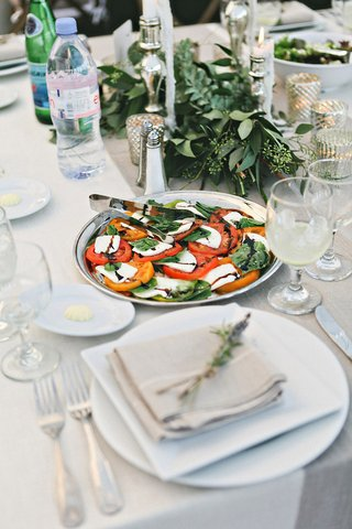 farm-wedding-reception-table-with-a-silver-platter-of-caprese-salad-greenery-garlands