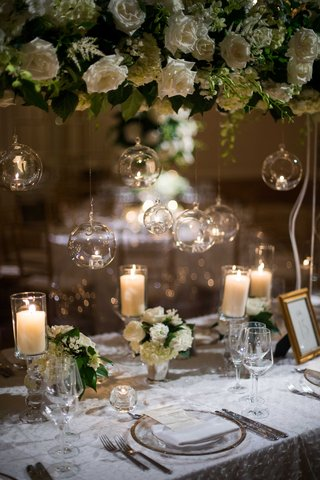 long-table-small-and-tall-floral-arrangements-white-flowers-foliage-hanging-glass-balls