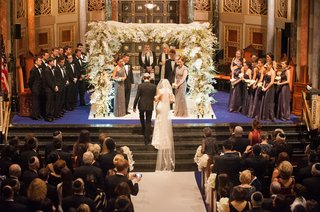 groom-leads-bride-to-four-post-chuppah-made-of-branches-and-decorated-with-white-orchids