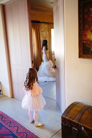 flower-girl-in-pink-cardigan-tulle-skirt-looks-at-bride