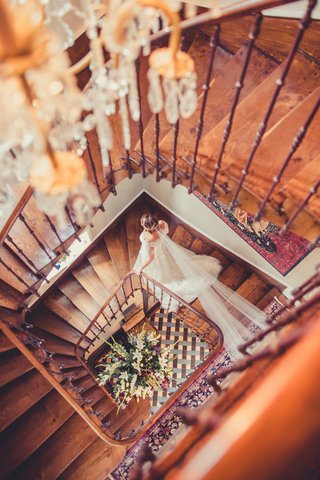 bride-in-wedding-dress-and-long-homemade-handmade-veil-walking-down-wood-staircase-at-french-venue