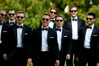 groom-and-groomsmen-in-black-tuxedos-bow-ties-sunglasses-white-pocket-squares