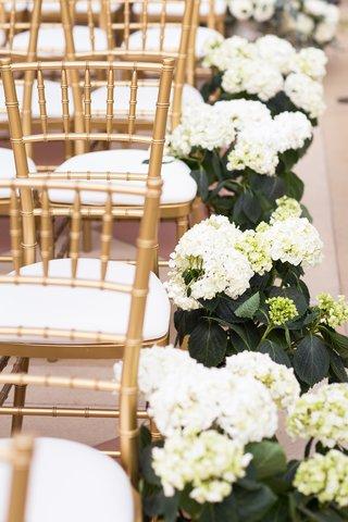 white-hydrangeas-along-aisle-next-to-gold-chiavari-chairs