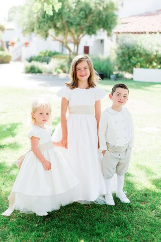 older-flower-girl-holding-hands-of-younger-flower-girl-and-ring-bearer-in-old-fashioned-attire