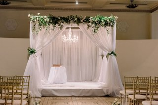 interfaith-ceremony-structure-with-white-drapery-greenery-and-chandelier