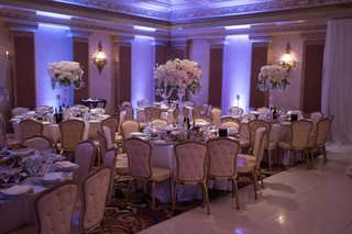 tufted-wedding-event-chairs-banquet-hall-violet-uplighting-candelabra-centerpiece-white-pink-flowers