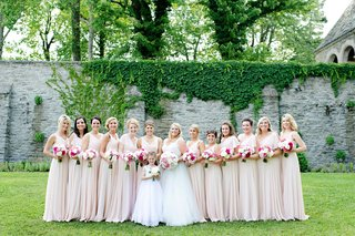 bride-with-twelve-bridesmaids-in-blush-dresses-mismatched-necklines-sleeves-white-flower-girl-dress