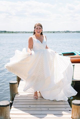 bride-in-striped-hayley-paige-wedding-dress-twirling-on-private-dock