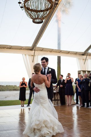 bride-and-groom-dancing-beneath-clear-reception-tent