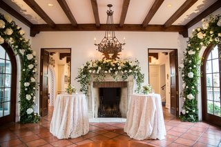 wedding-reception-cocktail-hour-decor-inside-bride-home-greenery-white-flower-arches-wood-beams