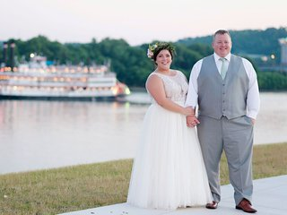 bride-in-sleeveless-wedding-dress-holding-grooms-hand-by-water-river-boat-groom-in-grey-vest