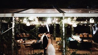 bride-and-groom-kiss-in-front-of-reception-tent-with-lounge-furniture-string-lights-boho-design