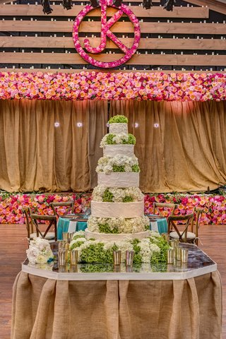white-wedding-cake-with-white-and-green-hydrangea-in-between-each-tier-on-a-mirror-tabletop
