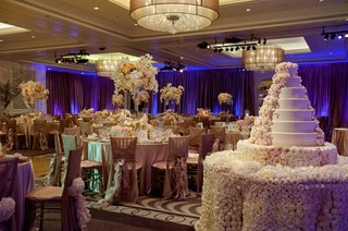 round-guest-tables-in-ballroom-next-to-wedding-cake