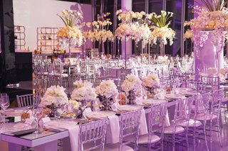 wedding reception ballroom long mirror table clear chairs low centerpiece design white decor