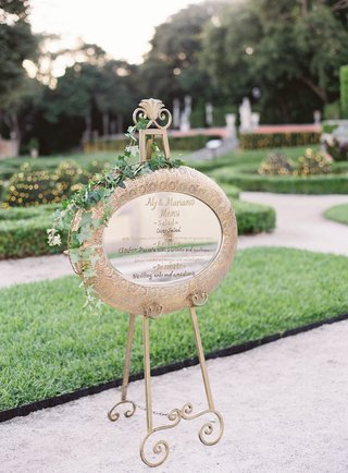 easel-with-gold-framed-mirror-gold-calligraphy-menu-greenery-vines-decorated-garden