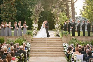 young-couple-on-top-of-steps-kissing-at-wedding