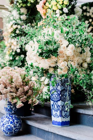 wedding ceremony steps blue and white vases chinoiserie with champagne rose flowers and greenery