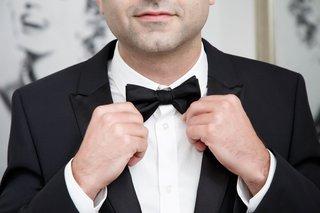 groom-in-tuxedo-wedding-day-tighten-bow-tie-wedding-day-accessories