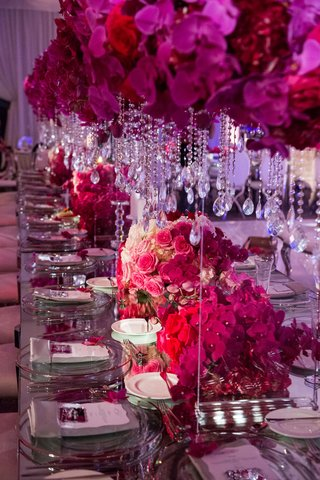 long-reception-table-with-pink-orchid-and-rose-flowers-crystal-strands-suspended-from-flowers