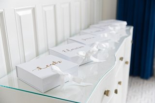 white-box-with-white-ribbon-gold-calligraphy-names-on-top-of-box-on-white-gold-dresser