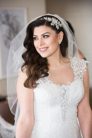 wedding photo of bride in bridal gown with long hair curls headpiece veil