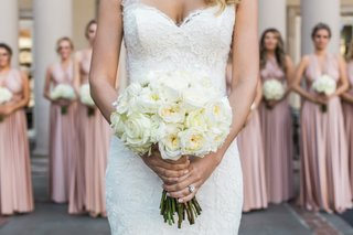 bride-holds-bouquet-with-bridesmaids-behind-her