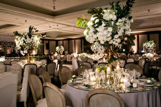 wedding reception ballroom cane wood chair mirror table white rose hydrangea greenery centerpieces