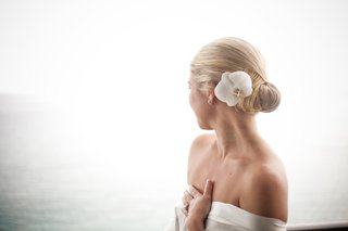 low-updo-bun-on-blonde-bride-wedding-hair-with-fresh-orchid-flower