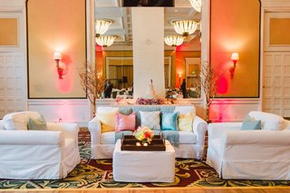 indoor-wedding-lounge-area-white-slipcover-sofas-and-ottoman-with-wood-tray-pink-and-blue-pillows