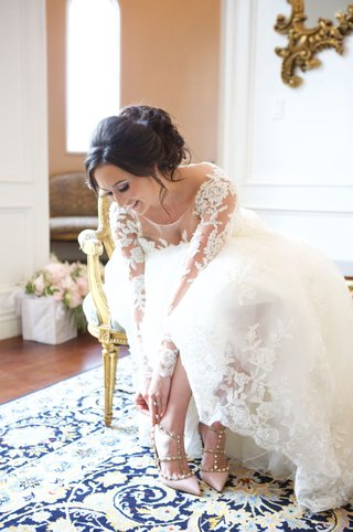 bride-in-wedding-dress-lace-illusion-long-sleeve-in-chair-putting-on-valentino-pumps-studs-pink
