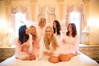 bride-in-white-robe-lace-trim-bridesmaids-in-light-pink-robes-on-bed-in-bridal-suite
