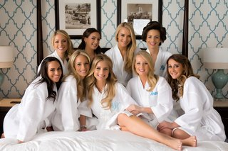 bride-and-bridesmaids-on-hotel-bed-with-white-robe-and-blue-monogram-gifts