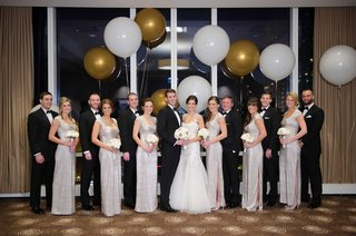 new-years-eve-bridal-party-in-front-of-window-and-large-gold-and-white-balloons
