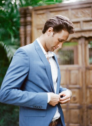 groom-in-relaxed-attire-no-tie-white-button-down-shirt-light-blue-suit-jacket-for-destination-weddin