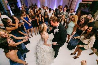 bride-in-demetrios-groom-in-ermenegildo-zegna-surrounded-by-friends-on-dance-floor