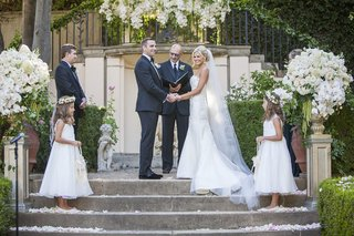 bride-and-groom-officiant-best-man-flower-girls-outdoor-courtyard-greenery-white-flowers-ceremony