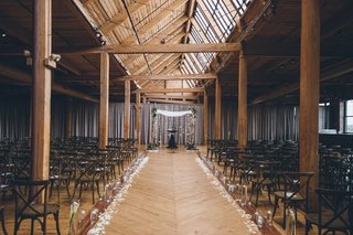 wood-beams-rustic-wedding-ceremony-venue-with-flowers-and-minimal-decor-birch-branches