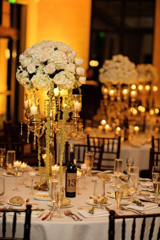 wedding-reception-table-with-golden-candelabra-topped-with-white-and-green-hydrangeas-white-roses