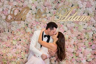 bride-in-blush-wedding-dress-groom-in-white-tuxedo-kiss-in-front-of-flower-wall