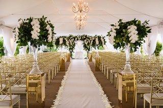 wedding-ceremony-white-tent-chandelier-aisle-runner-flower-petal-lined-riser-white-orchid-greenery