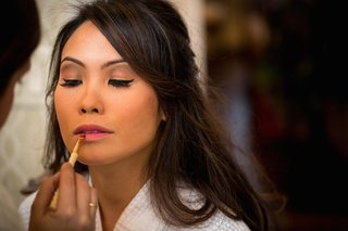 makeup-artist-finishes-brides-look-with-light-pink-lipstick