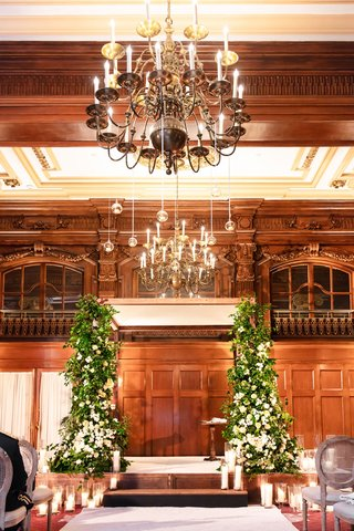 wedding-ceremony-wood-paneled-ballroom-greenery-white-flower-chuppah-candles-oval-back-wood-chairs