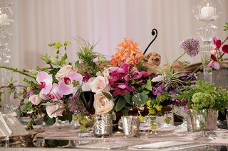 pink-orchids-ivory-roses-orange-flowers-greenery-votives-in-mercury-glasses