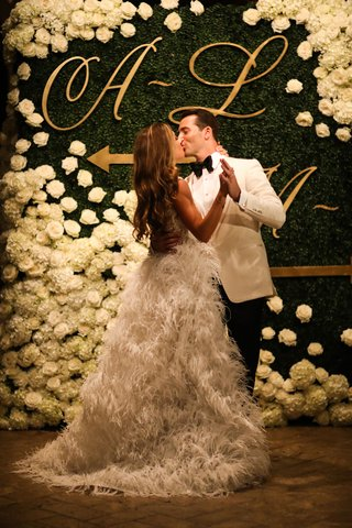 bride-in-second-wedding-dress-ostrich-feather-skirt-kissing-groom-in-front-of-hedge-wall-chart