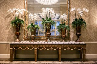 wedding-reception-escort-card-table-damask-wallpaper-gold-console-table-orchid-in-urns-luxury-hotel