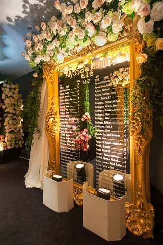 gold-oversized-mirror-with-flowers-on-top-displaying-calligraphy-names-of-guests-and-their-tables